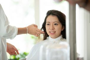 美容師にヘアセットをしてもらう女性の写真素材 [FYI01956966]