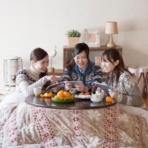 こたつでゲームをする3人の女性の写真素材 [FYI01956978]