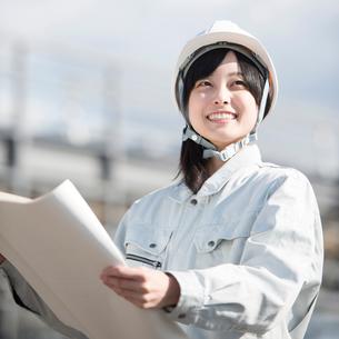 図面を持ち微笑む作業員の写真素材 [FYI01957009]