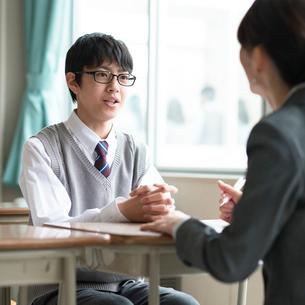 進路相談をする男子学生と女性教師の写真素材 [FYI01957043]