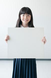 ホワイトボードを持ち微笑む小学生の写真素材 [FYI01957072]