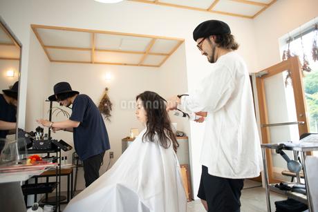 美容師にヘアセットをしてもらう女性の写真素材 [FYI01957199]