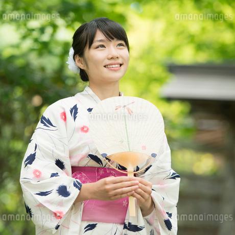 うちわを持ち微笑む浴衣姿の女性の写真素材 [FYI01957264]