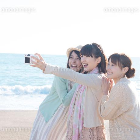 海で写真を撮る3人の女性の写真素材 [FYI01957304]