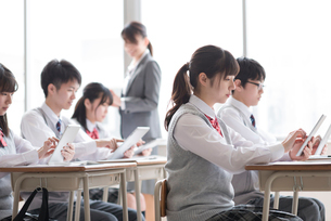 タブレットPCで勉強をする学生と女性教師の写真素材 [FYI01957306]