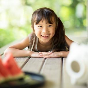縁側に寝転び微笑む女の子の写真素材 [FYI01957321]