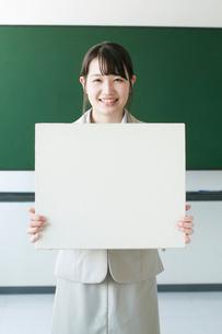 ホワイトボードを持ち微笑む先生の写真素材 [FYI01957342]