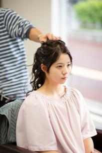 美容師にヘアセットをしてもらう女性の写真素材 [FYI01957357]