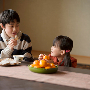こたつで干し芋とみかんを食べる兄妹の写真素材 [FYI01957383]