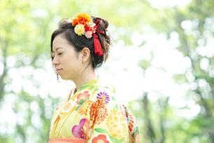 森林の中で目を閉じる着物姿の女性の写真素材 [FYI01957422]