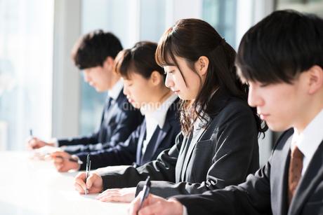 筆記試験を受けるビジネスマンとビジネスウーマンの写真素材 [FYI01957448]