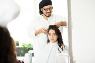 美容師にヘアセットをしてもらう女性の写真素材 [FYI01957487]