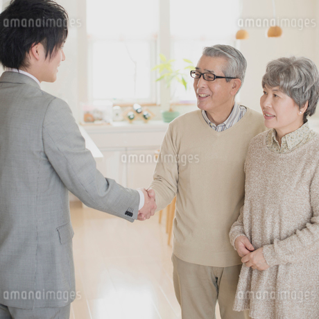 ビジネスマンと握手をするシニア夫婦の写真素材 [FYI01957491]