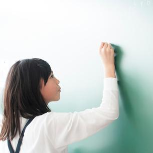 黒板の前でチョークを持つ小学生の写真素材 [FYI01957497]