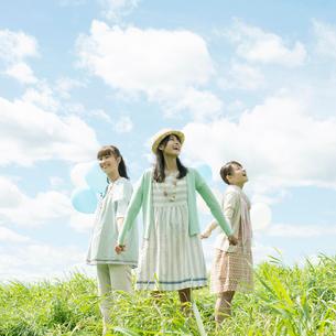 草原で手をつなぐ3人の女性の写真素材 [FYI01957500]