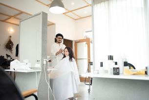 美容師にヘアセットをしてもらう女性の写真素材 [FYI01957526]