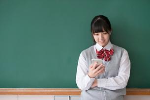 スマートフォンで音楽を聴く女子学生の写真素材 [FYI01957531]