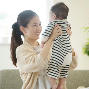 赤ちゃんを抱き微笑む母親の写真素材 [FYI01957536]
