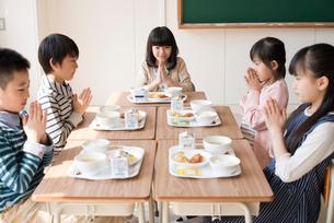 給食を前に手を合わせる小学生の写真素材 [FYI01957596]