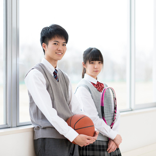 テニスラケットとバスケットボールを持ち微笑む学生の写真素材 [FYI01957602]
