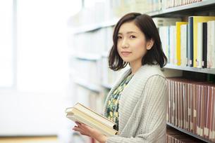 図書館で本を持ち微笑む女性の写真素材 [FYI01957633]