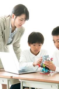 先生にプログラミングの勉強を教わる小学生の写真素材 [FYI01957649]