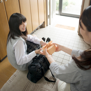 玄関で娘にお弁当を渡す母親の写真素材 [FYI01957679]