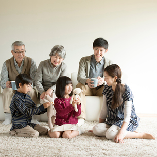 ソファーの周りでくつろぐ3世代家族の写真素材 [FYI01957753]