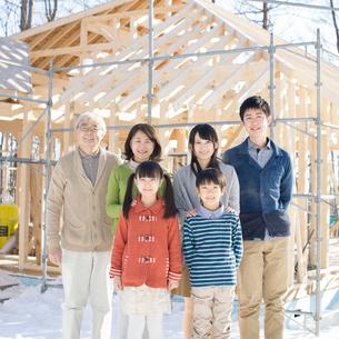 建設途中の家の前で微笑む3世代家族の写真素材 [FYI01957790]