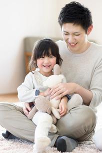 クマのぬいぐるみで遊ぶ親子の写真素材 [FYI01957801]