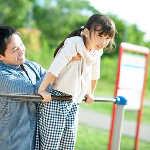 父親に鉄棒を教わる女の子の写真素材 [FYI01957831]