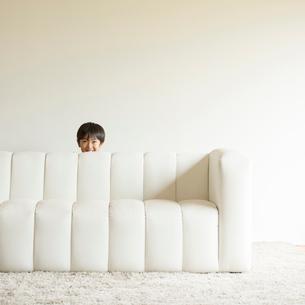 ソファーの後ろから顔を出す男の子の写真素材 [FYI01957879]