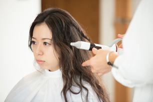 美容師にヘアセットをしてもらう女性の写真素材 [FYI01957898]