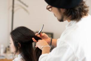 美容師にヘアセットをしてもらう女性の写真素材 [FYI01957913]