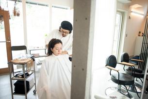 美容師にヘアセットをしてもらう女性の写真素材 [FYI01957918]