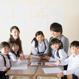 グループ学習をする小学生と先生の写真素材 [FYI01958060]