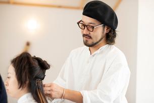 女性のヘアセットをする美容師の写真素材 [FYI01958092]