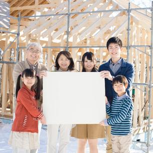 建設途中の家の前でメッセージボードを持ち微笑む3世代家族の写真素材 [FYI01958098]