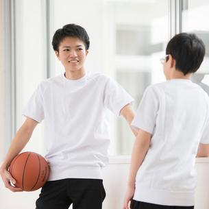 廊下でバスケットボールを持ち談笑をする男子学生の写真素材 [FYI01958121]