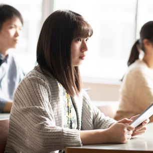 タブレットPCを持ち真剣な表情をする女子学生の写真素材 [FYI01958223]