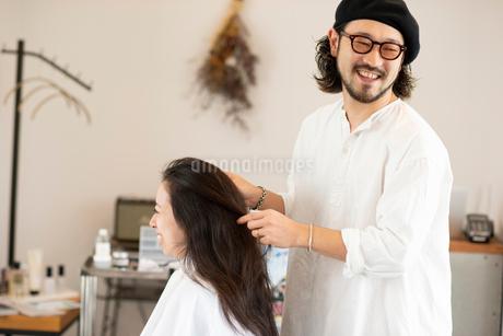 女性のヘアセットをする美容師の写真素材 [FYI01958243]