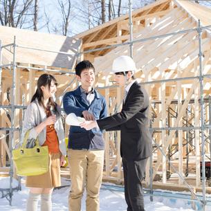 建設途中の家の前でビジネスマンと話をする夫婦の写真素材 [FYI01958267]