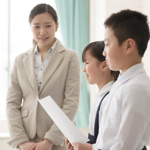 発表をする小学生と先生の写真素材 [FYI01958277]