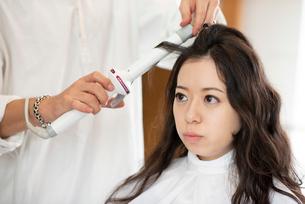 美容師にヘアセットをしてもらう女性の写真素材 [FYI01958349]