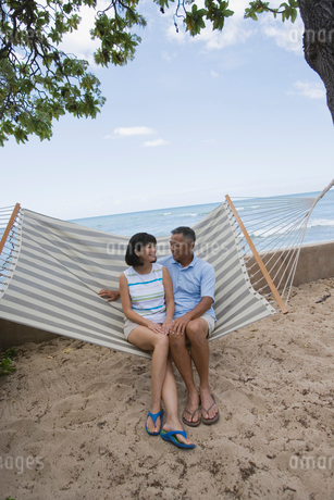 ハンモックに座るシニア夫婦の写真素材 [FYI01960449]