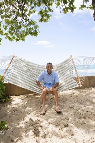 ハンモックに座るシニア男性の写真素材 [FYI01960759]