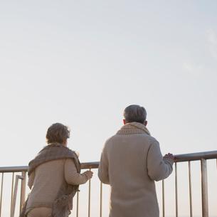 景色を眺めるシニア夫婦の後姿の写真素材 [FYI01960924]