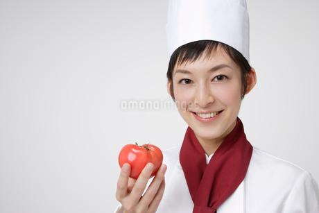 トマトを持つシェフの写真素材 [FYI01963716]