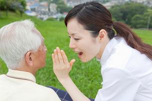 車椅子の男性に話しかける女性介護士の写真素材 [FYI01965991]