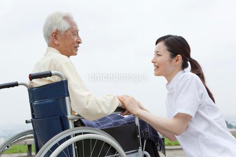 車椅子の男性と会話をする女性介護士の写真素材 [FYI01967946]